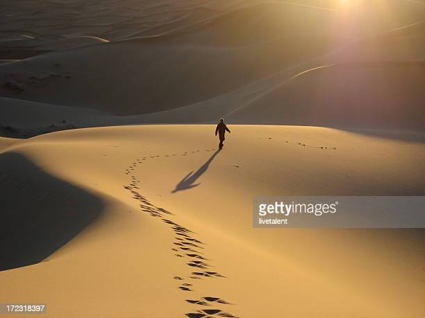 Man walking dunes at sunrise