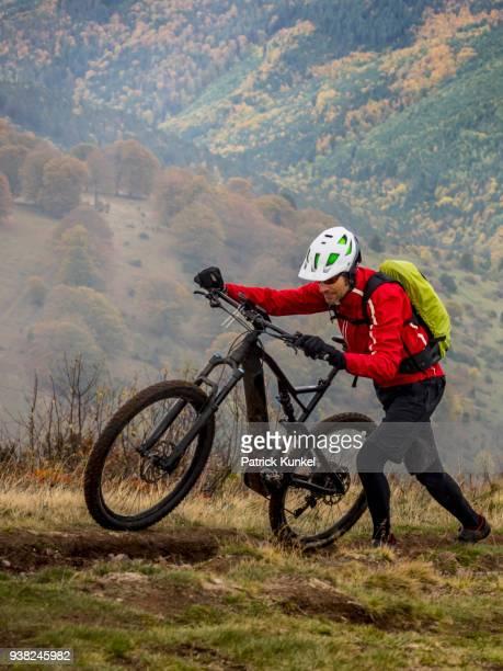 Man walking electric mountain bike on cycling tour, Vosges, France