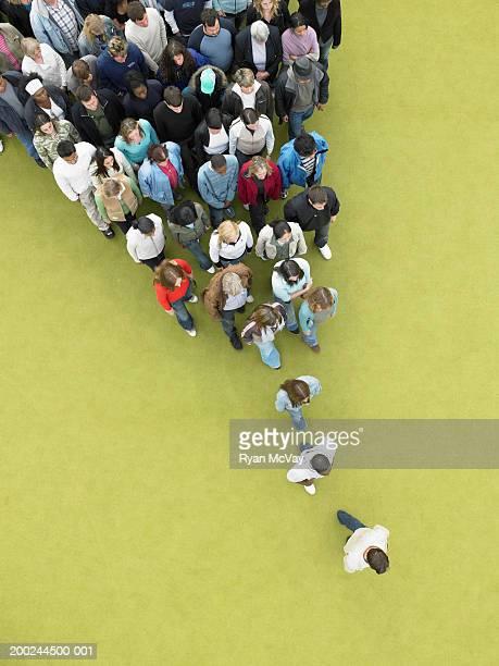Man walking, followed by gradually increasing crowd, overhead view