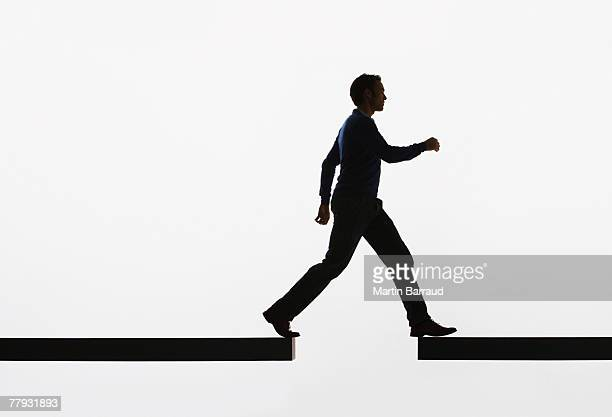 Man walking from a plank onto another plank
