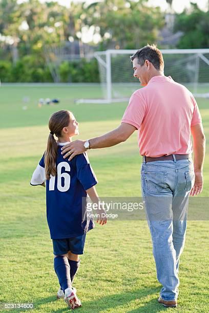 Man walking his daughter across soccer field