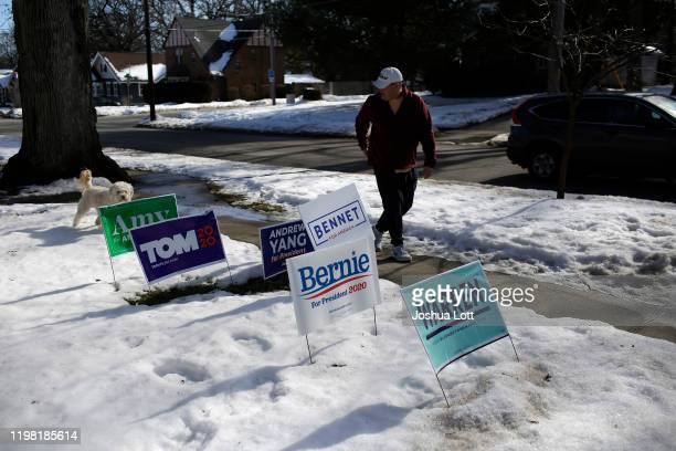 Man walking his dog walks past Democratic presidential campaign signs displayed in a front yard of a home campaign on February 2, 2020 in Des Moines,...