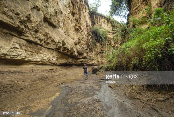 man walking in a canyon stream - kenya stock pictures, royalty-free photos & images
