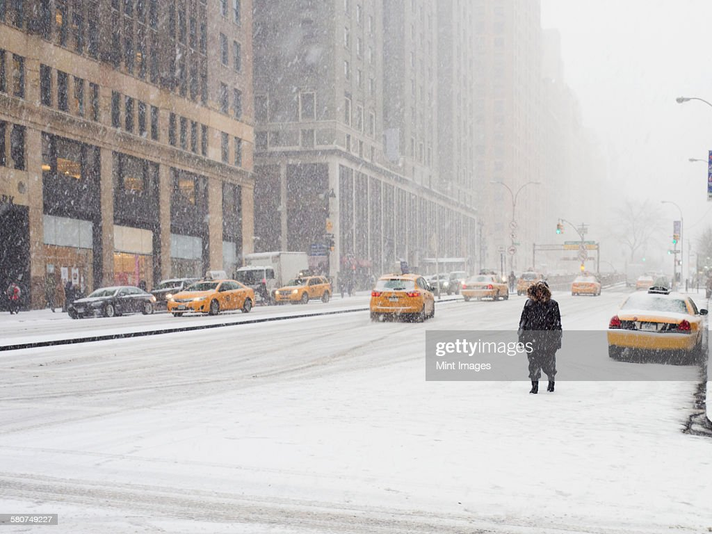 Man walking in a city in the snow during a blizzard, yellow taxis on the street. : Stock Photo