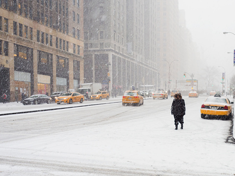 Man walking in a city in the snow during a blizzard, yellow taxis on the street. - gettyimageskorea