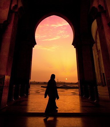 A man walking in a mosque during a sunset 117147403