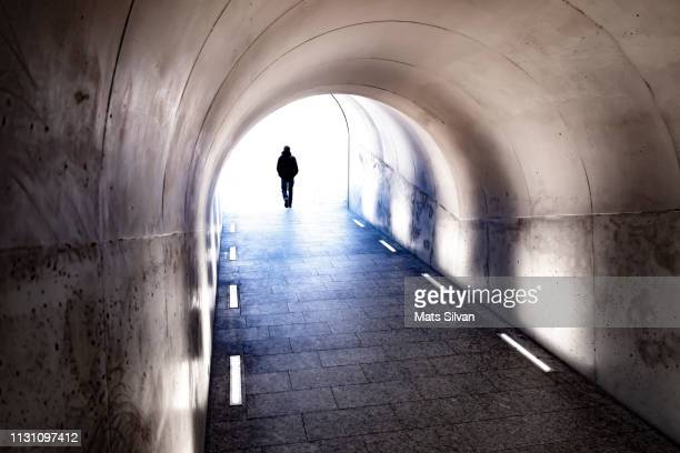 man walking in a tunnel with sunlight - light at the end of the tunnel stock pictures, royalty-free photos & images