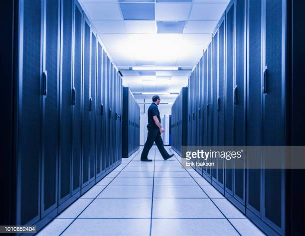 man walking in aisle of server room - data center stock pictures, royalty-free photos & images