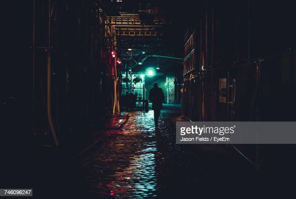 man walking in alley at night - escena del crimen fotografías e imágenes de stock