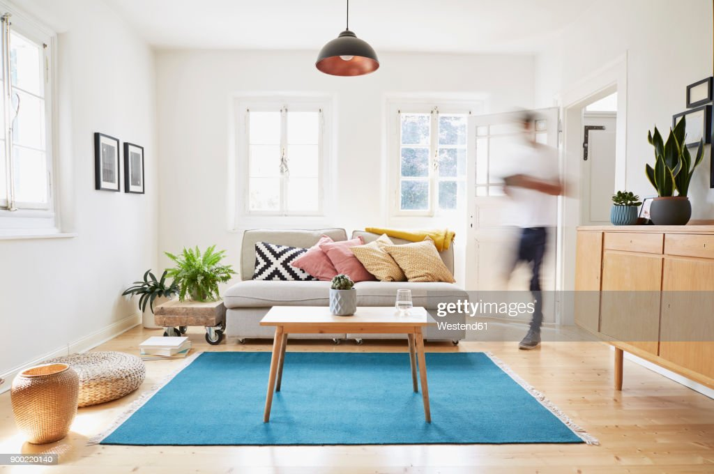 Man walking in bright modern living room in an old country house : Stock Photo