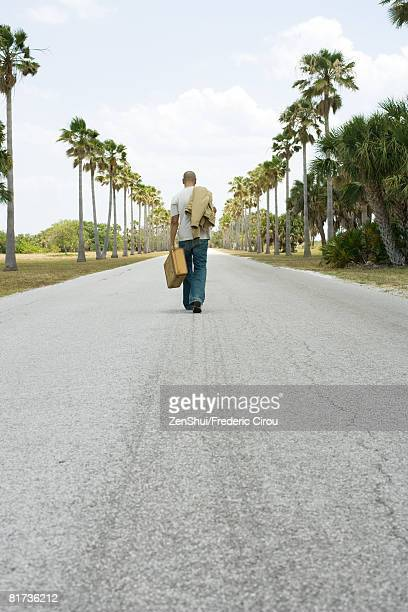 man walking in center of road, carrying suitcase and jacket, rear view - runaway stock pictures, royalty-free photos & images