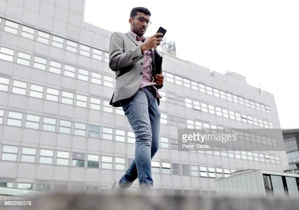 man walking in city looking at mobile phone - one man only stock pictures, royalty-free photos & images