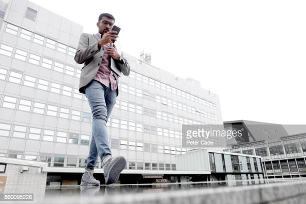 Man walking in city looking at mobile phone