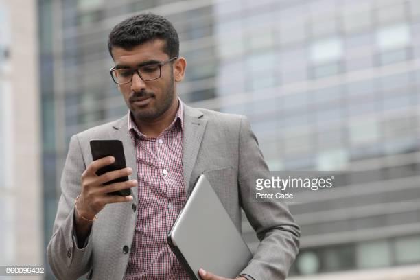 Man walking in city looking at mobile phone