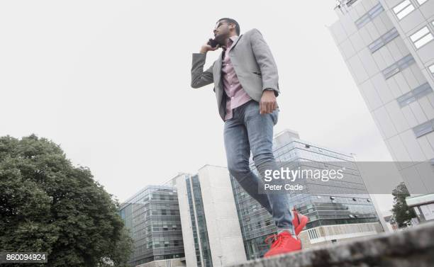man walking in city talking on mobile phone - blue blazer stock pictures, royalty-free photos & images