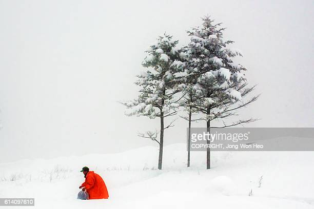 A man walking in deep snow with red coat