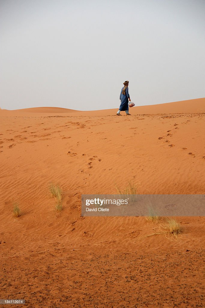 Man walking in desert : Stock Photo
