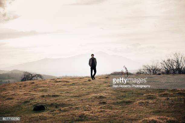 man walking in field - back lit stock pictures, royalty-free photos & images