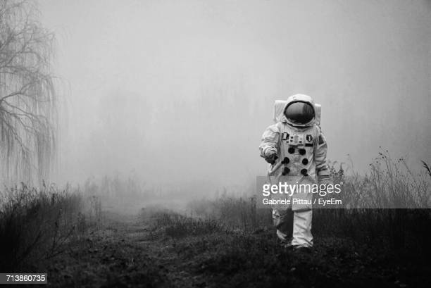 man walking in fog - space helmet stock pictures, royalty-free photos & images