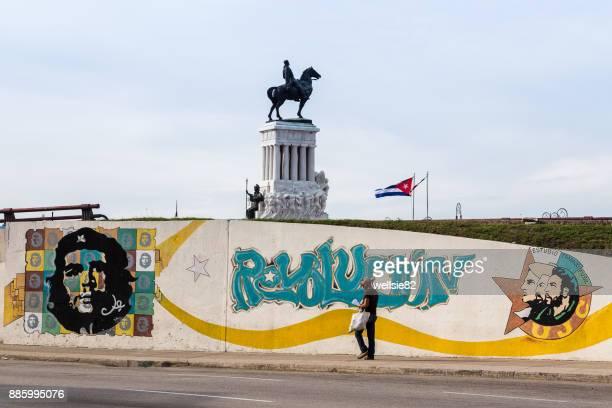 Man walking in front of a Cuban Revolution motif