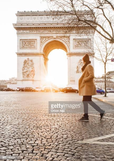 Homme qui marche en face de l'Arc de Triomphe