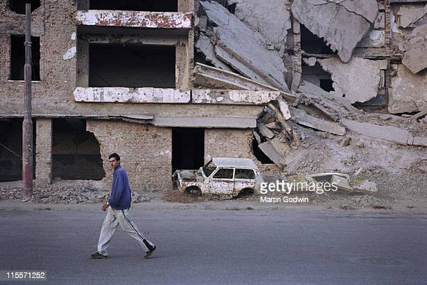 Man walking in front of destroyed buildings in central Kabul with rubble and the wreck of a car with shrapnel damage November 2002