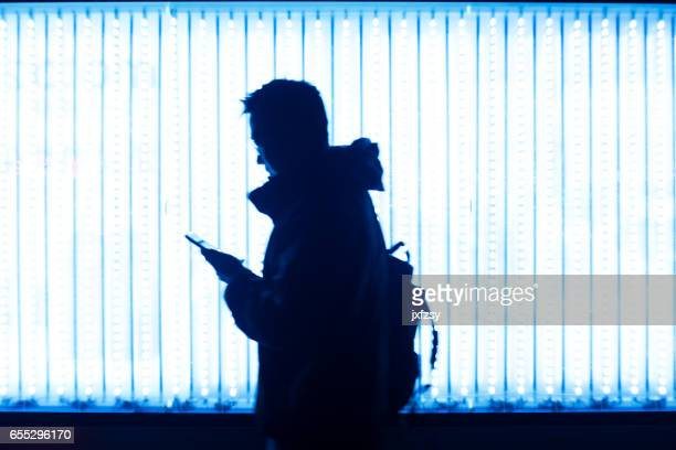 man walking in front of LED light