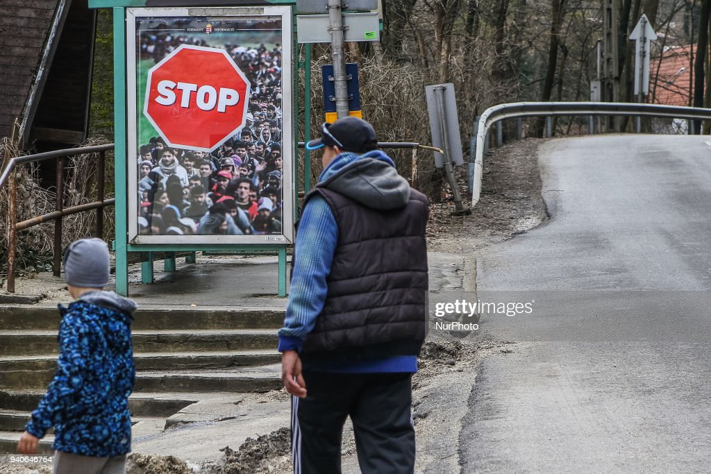 Man walking in front of official government anti-immigrants banner displayed on bus stop is seen in Miskolc, Hungary on 31 March 2018 According Hungarian media Victor Orban electoral posters are illegal as has no clearly designation of the source of origin, as the election material of the Hungarian government or the Fidesz political party