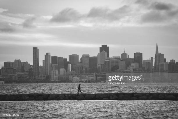 Man walking in front of San Francisco skyline, California