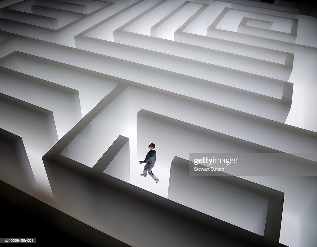Man walking in giant maze : Stock Photo