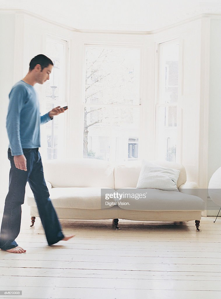 Man Walking in his House and Checking his Text Messages : Stock Photo