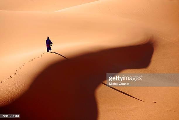 man walking in libyan desert - nomadic people stock pictures, royalty-free photos & images