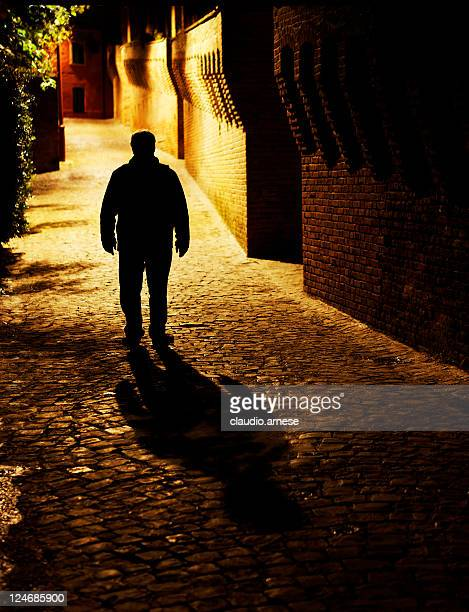 man walking in medieval alley. color image - alley stock pictures, royalty-free photos & images