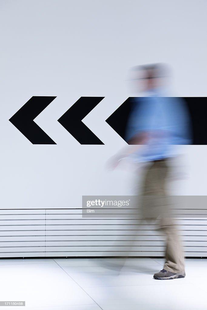 Mann zu Fuß in entgegengesetzte Richtung der Pfeil : Stock-Foto