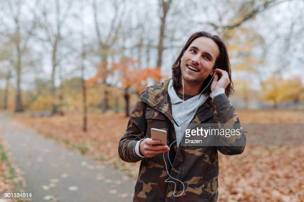 Man walking in park in autumn and listening to radio podcast