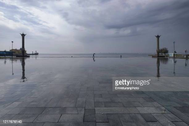man walking in republic square on a rainy day,izmir. - emreturanphoto stock pictures, royalty-free photos & images