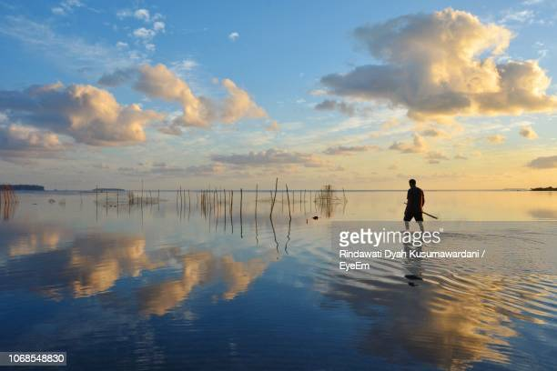 man walking in sea against sky during sunset - nuku'alofa stock pictures, royalty-free photos & images
