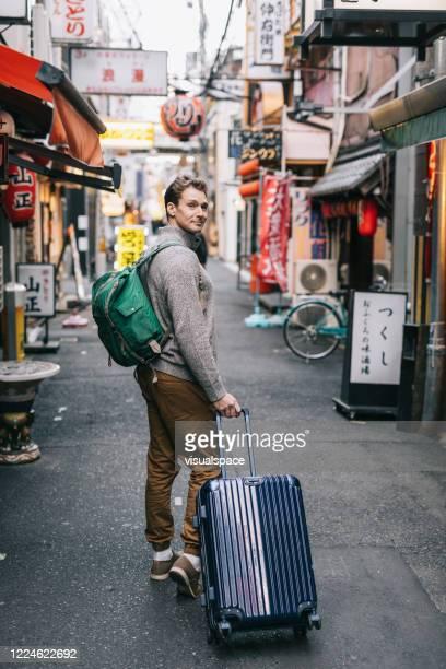 homem andando em pequenos becos para descobrir as verdadeiras vibrações na cidade - looking over shoulder - fotografias e filmes do acervo