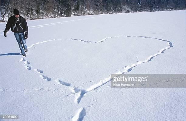Man walking in snow, making heart shape by footprint
