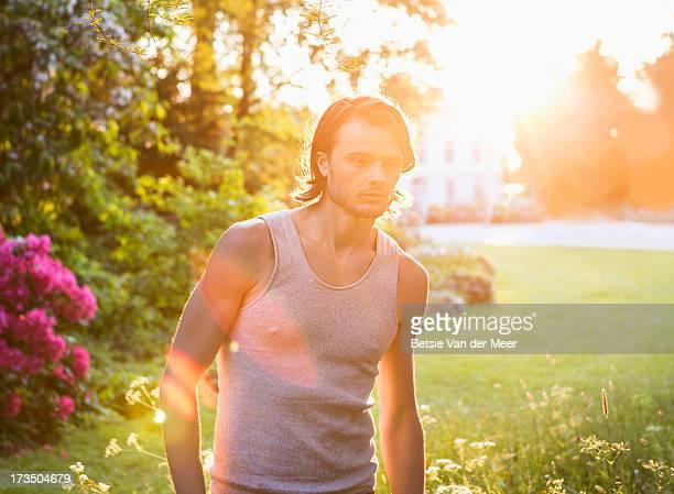 Man walking in sunshine in urban green area.