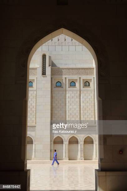 Man walking in the exterior courtyard of the Sultan Qaboos Grand Mosque, in Muscat, Oman, framed by arch