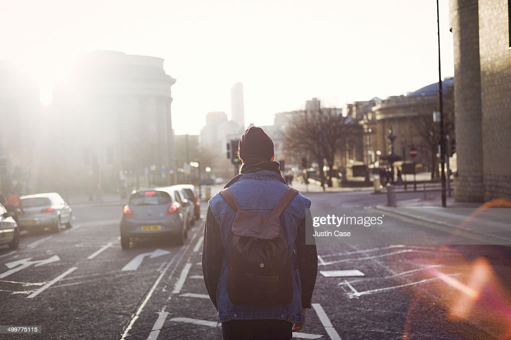 man walking in the middle of a city road : Stock Photo