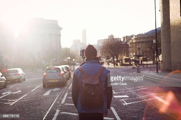 man walking in the middle of a city road