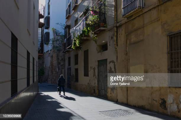 a man walking in the middle of a narrow street with strong sunlight and dark shadows - dorte fjalland stock pictures, royalty-free photos & images