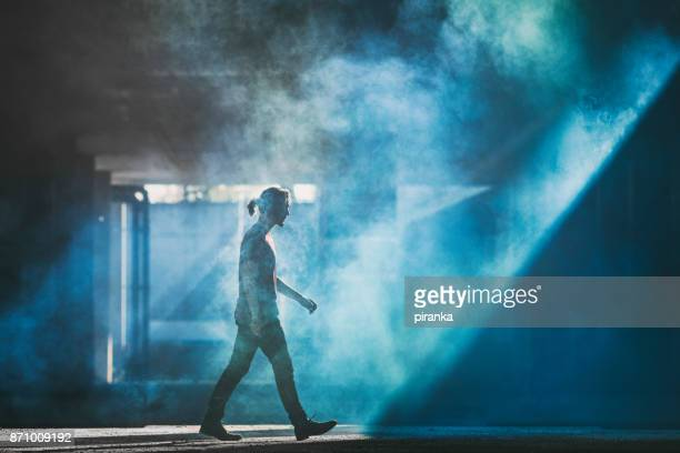 man walking in the smoke - spotlit stock pictures, royalty-free photos & images