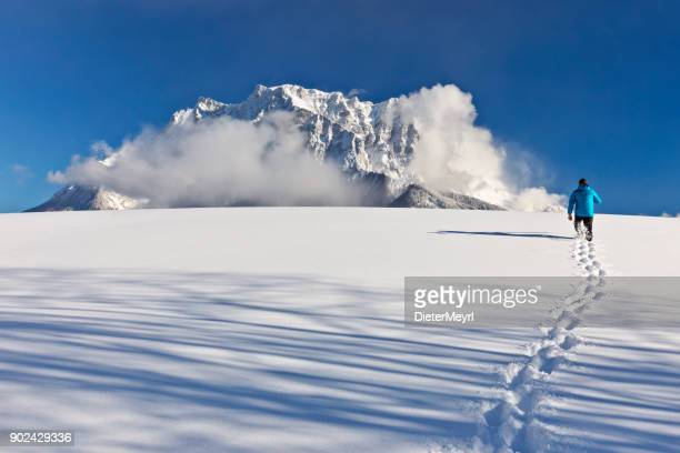 Man Walking in the Snow in front of Mount Zugspitze
