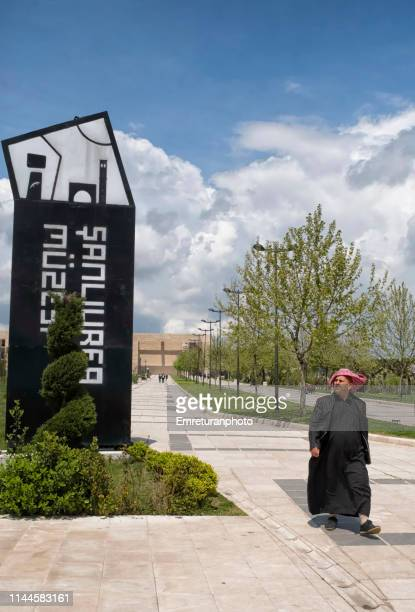 man walking in traditional clothing and museum sign,şanlıurfa. - emreturanphoto stock pictures, royalty-free photos & images