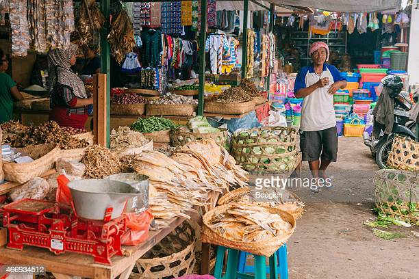 man walking in traditional indonesian farmer's market in rural bali - denpasar stock pictures, royalty-free photos & images