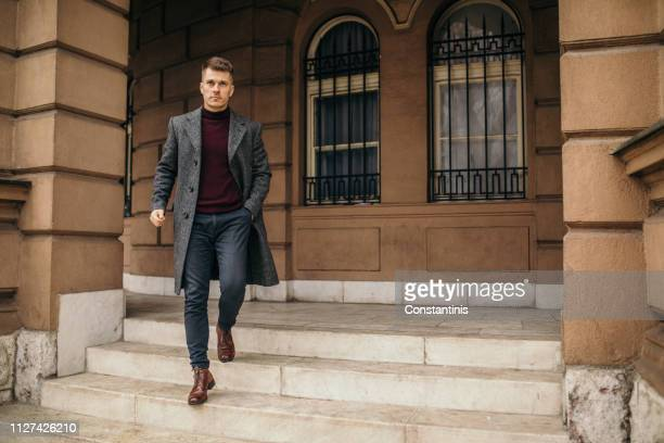 man walking in urban setting - coat stock pictures, royalty-free photos & images