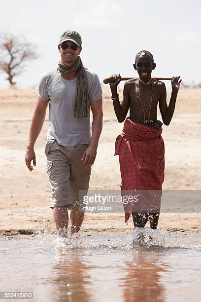 man walking in water with tribesman - hugh sitton stock pictures, royalty-free photos & images